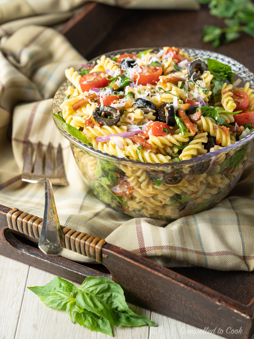 Prepared Mediterranean Pasta Salad served in a clear bowl on a wooden tray.