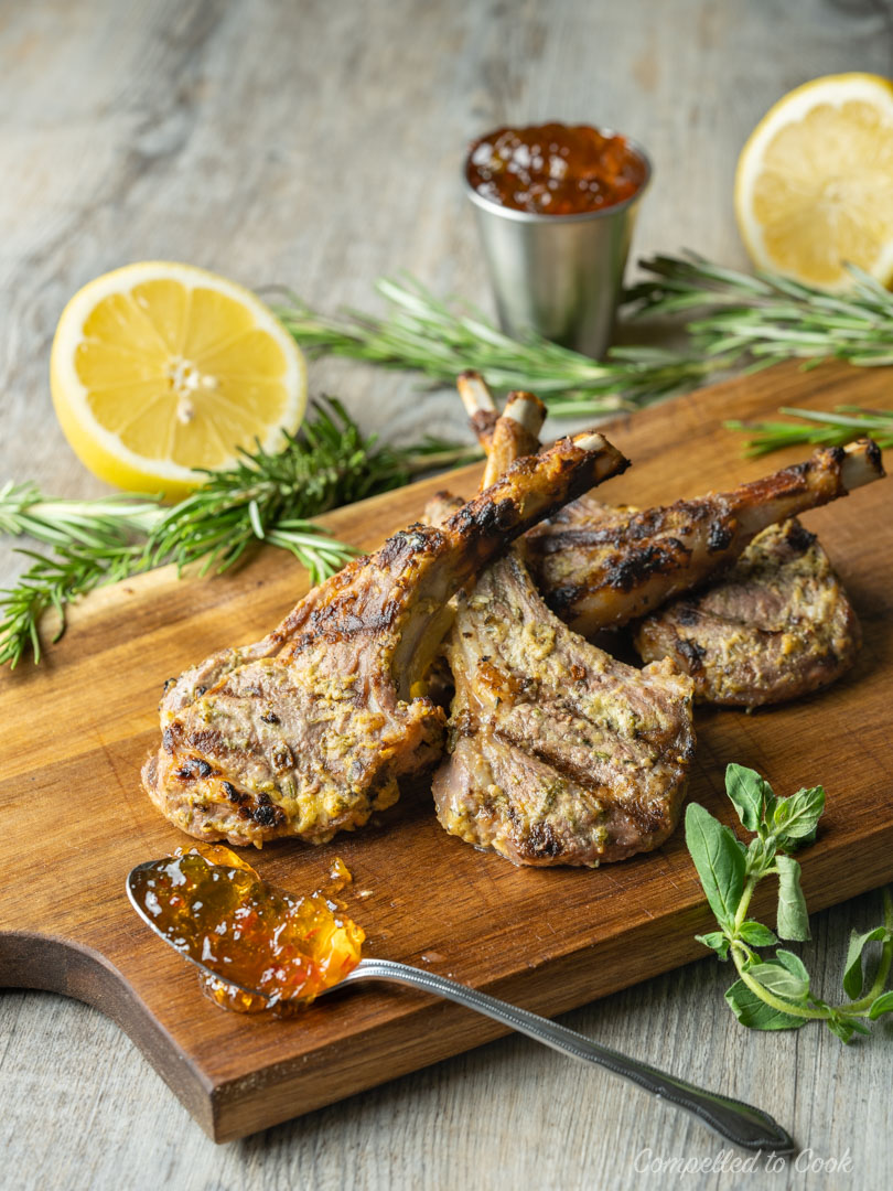 Grilled Lamb Chops garnished with fresh herbs and served on a wooden board.