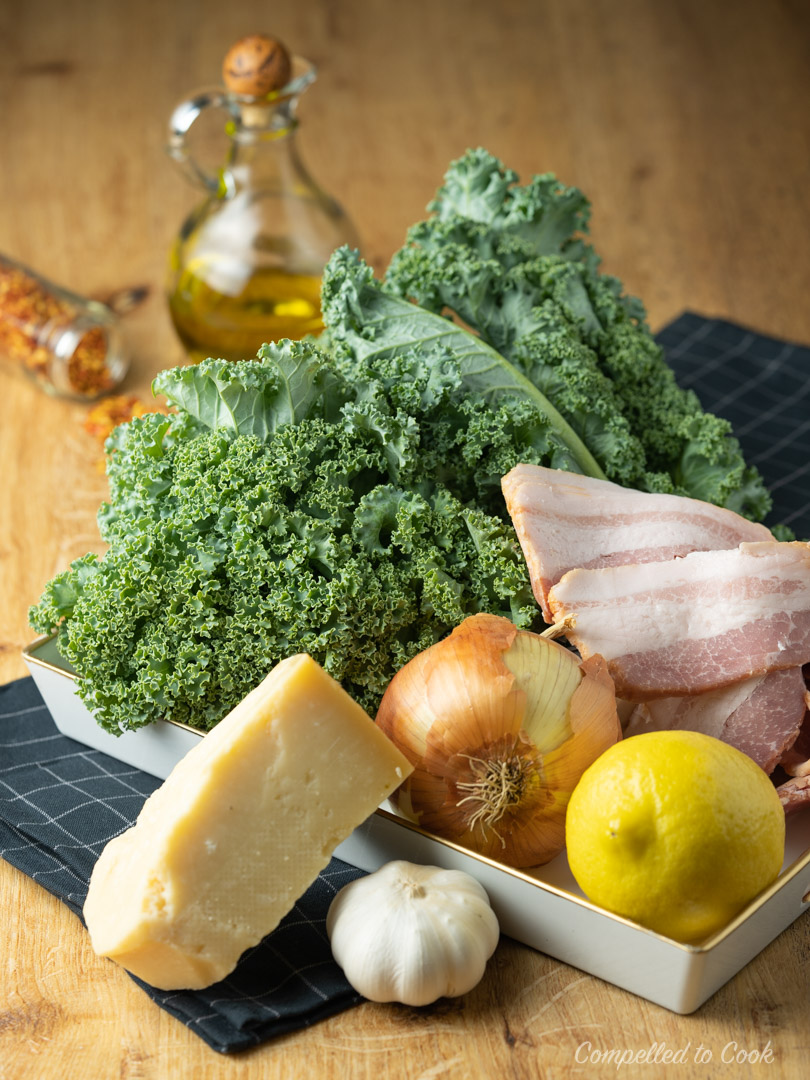 Ingredients for Braised Kale with Bacon nestled in a shallow white tray.