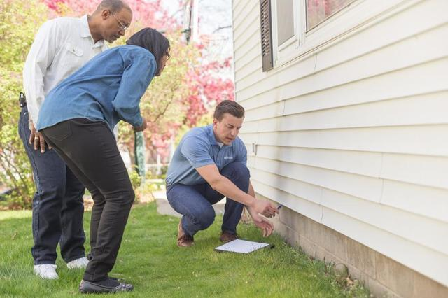 Design Specialist inspecting home