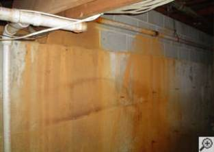 Iron ochre stains on a basement wall, where the pipes have leaked.