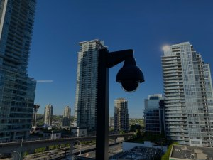 A photo of a cctv camera on a pole looking out over the city.