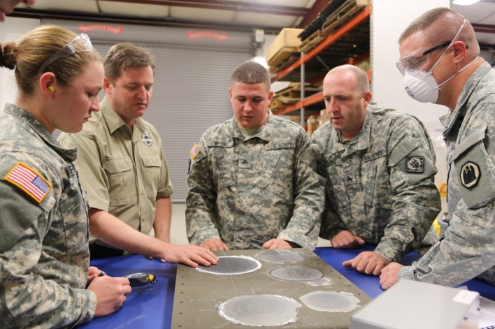 Earl Thomas, lead composite instructor, instructs National Guard Soldiers on inspecting a composite repair.
