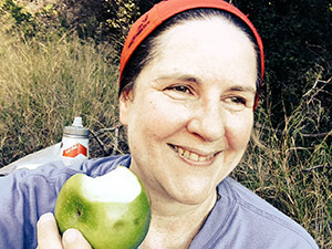 Laurie in a red scarf eats a green apple in a field of grass