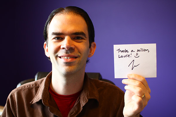 "Josh Woodward holds a sign saying ""Thanks a Million Laurie!"""