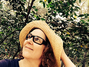 Laurie holds back her hat brim under the Camellia bushes