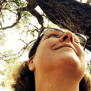 Laurie looks up under an oak tree