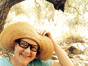 Laurie holds her hat brim up away from her face.