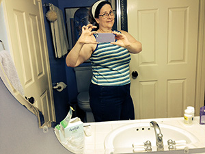 Laurie in the mirror wearing jeans and sleeveless top.