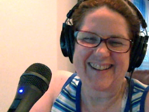 Laurie in headphones near a microphone.