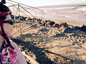 Laurie in bike gear looking out at waves on a beach