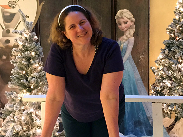 Laurie leans on a white bridge with characters from Frozen and white Christmas trees in the background