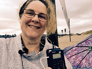 Laurie holds her recorder up by her face on a stormy day on the beach