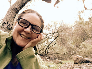 Laurie with cheek in hand wearing glasses and a green fleece jacket by the podcast tree at the park