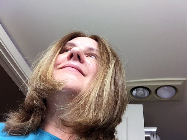 Shot of Laurie looking up - featuring her salon ready shoulder length hair with blonde streaks and NO grey!