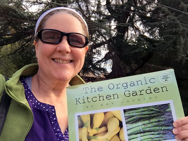 Laurie holding a calendar entitled, The Organic Kitchen Garden