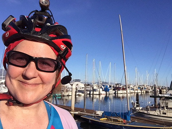 Laurie in bike gear in front of boats at dock in the harbor.