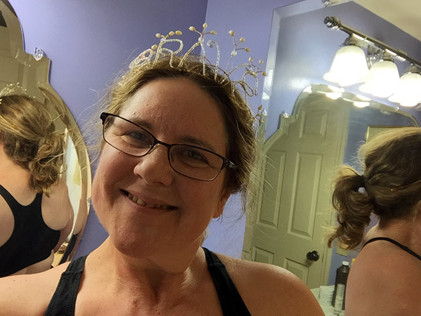 Laurie looking in the bathroom mirror while wearing a tiara that says 'BRAVE'.