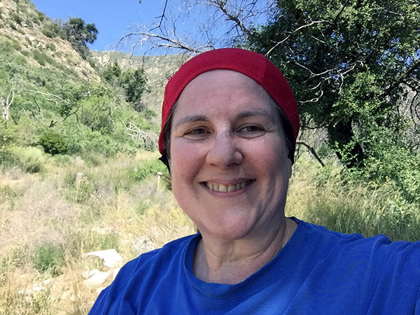 Laurie in her red hiking scarf in front of the trail