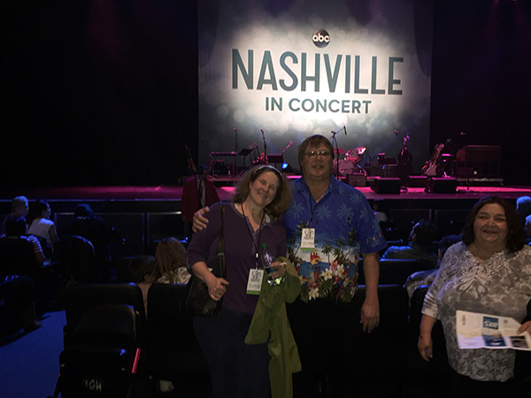 Laurie and Mark standing in front of the stage with the NASHVILLE in Concert sign in back