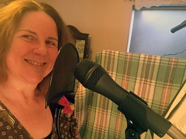 Laurie in front of a mic in her guest room recording space