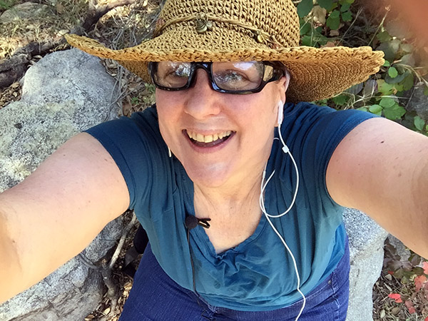 Laurie on the podcast rock wearing a straw hat and smiling hugely
