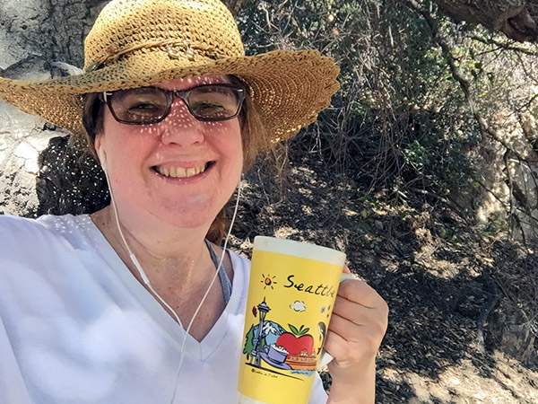 Laurie holding a coffee mug that has cartoon items representing Seattle on the trail in the park