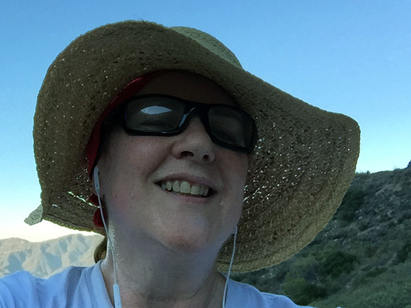 Laurie in straw hat on the hiking trail