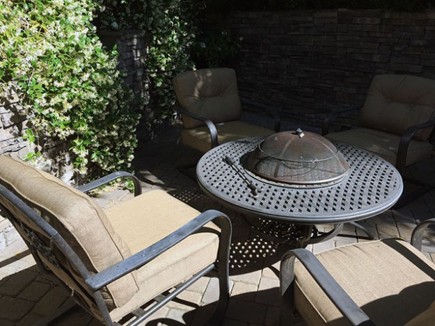 Comfy chairs around a black iron fire pit on a stone patio