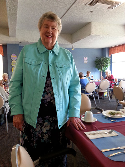 Laurie's Mom models a turquoise leather coat in the dining room of her retirement home.