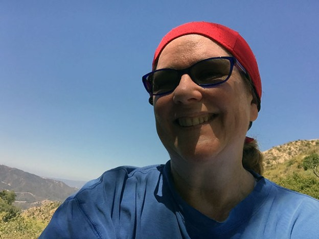 Laurie in red head scarf and blue long sleeved shirt at top of trail with bright cloudless sky behind - face in shadow