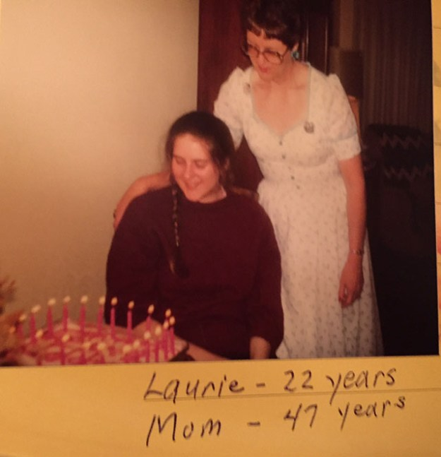 Young lady Laurie with a braid over one shoulder and Mom in a formal looking over at a lit birthday cake