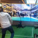 Hombre interactuando con video wall mediante juego de realidad aumentada