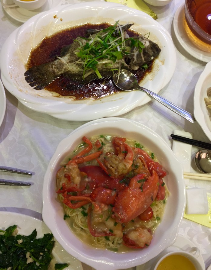 A plate of steamed fish and another of lobster with noodles.