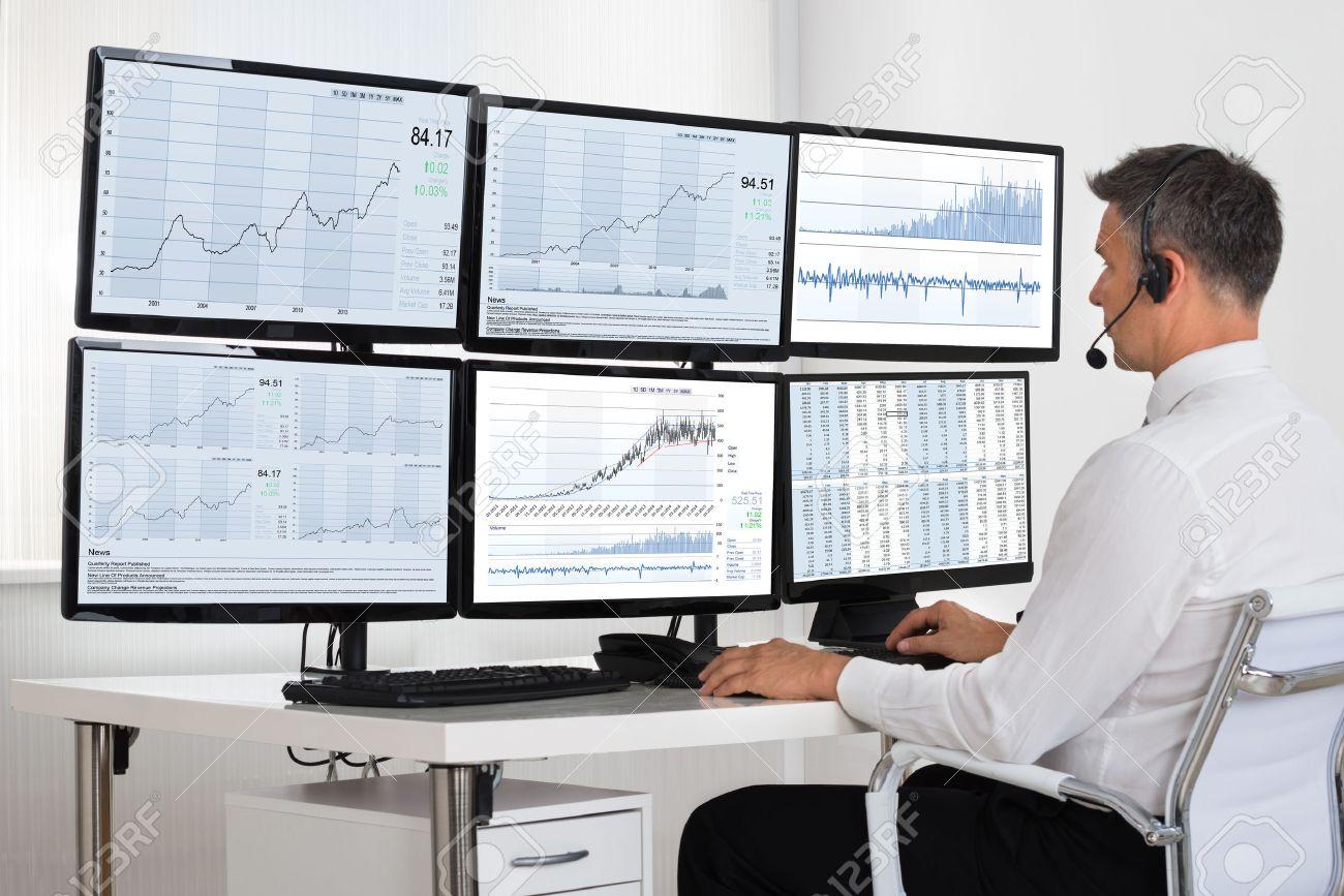 51090724-vista-lateral-del-corredor-de-bolsa-mirando-gráficos-en-múltiples-pantallas-en-la-oficina