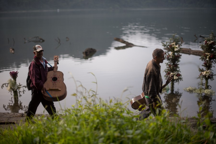 Two musicians walks around lake Chicabal singing narco corridos. Photo: Santiago Billy/Comvite