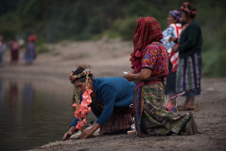 A woman plants a flower as she arrives to the shores of lake Chicabal. Photo: Santiago Billy/Comvite