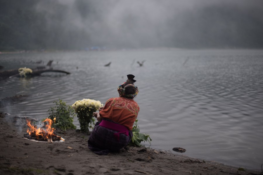 A woman beside a ritual fire on the shores of lake Chicabal as mist starts to cover the volcanic lake. Photo: Santiago Billy/Comvite