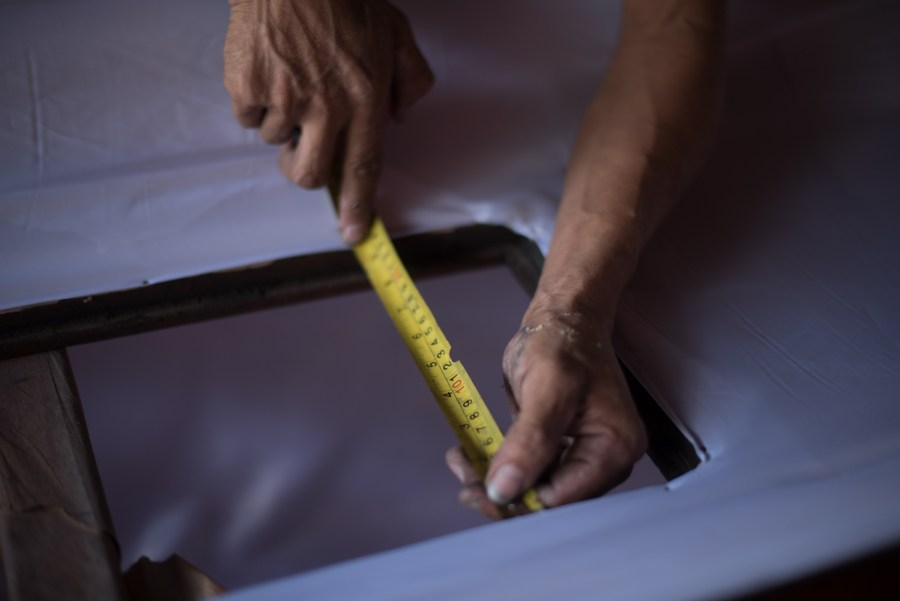 A man measures the glass hole on a casket in order to preciselly cut a piece of glass.