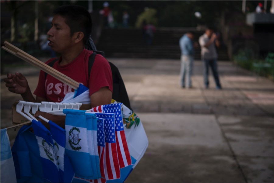 A man selling flags of Guatemala and the United States of America, Guatemala city, Guatemala. Photo: Santiago Billy/Comvite