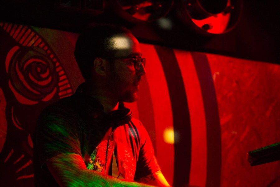 A Dj while playing music, being illuminated by lasers and red light in Guatemala City. Photo: Jose Hernandez/Comvite
