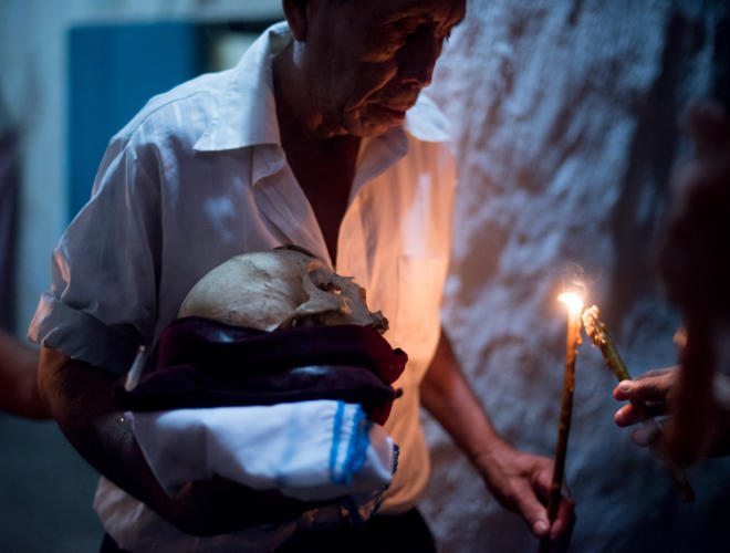 A faithful returns the skull to the procession after paying respects in his family home. San José, Petén, northern Guatemala. Photo: Santiago Billy/Comvite