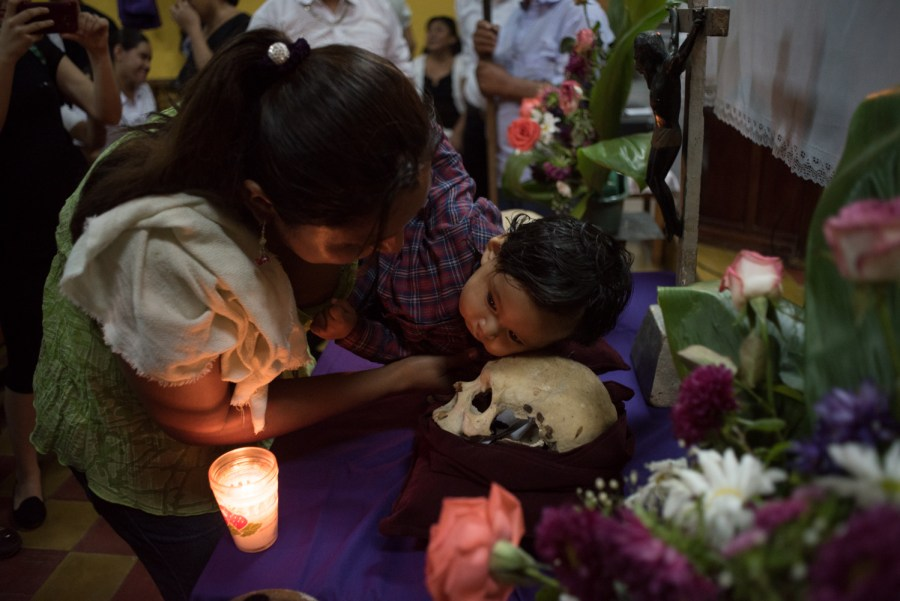 A woman holds her child so he can kiss one of the three skulls that represent the ancestors of the Maya Itza at the Catholic Church, prior to the procession of The Holy Spirits, in San José Petén, northern Guatemala. Photo: Santiago Billy/Comvite