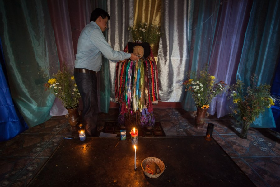 Nicolas Tziná, a Maya curer in Santiago Atitlan, tends a statue of his private Ril Aj Mam. Photo: Jeff Abbott/Comvite