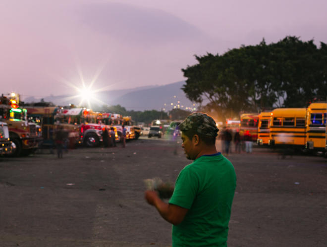 An ayudante, or camioneta driver's assistant, counts money while waiting for the bus to fill up with customers and depart Antigua, Guatemala, on Tuesday, January 17, 2017. Photo:Rachel Eubanks/Comvite