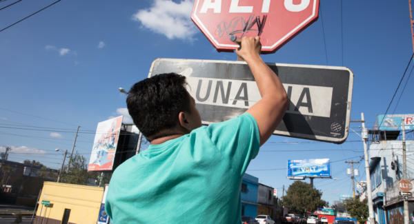 Seyor, a graffiti artist, tags a stop sign in Guatemala City. Photo: Hyungsup Kim/Comvite