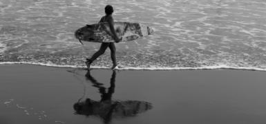 Lucero Batres, 11, walks across the beach while Nery Batres surfs on the waves. Photo: Santiago Billy/Comvite
