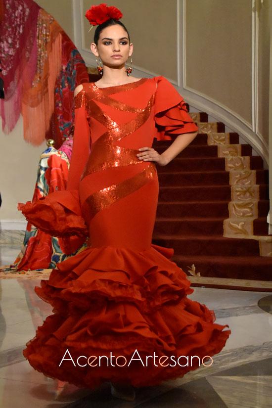 Traje de flamenca en rojo de talle bajo y asimetría en mangas de Yolanda Rivas para Úniqo Qlamenco