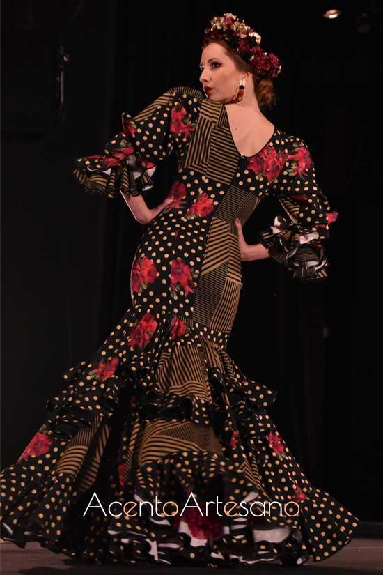 Traje de flamenca negro de lunar amarillo, rayas al tono y flor de granada, en el que las mangas jamón acompañan al talle bajo diseñado por Ajolí 58