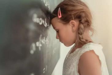 Mädchen lehnt deprimiert an Tafel